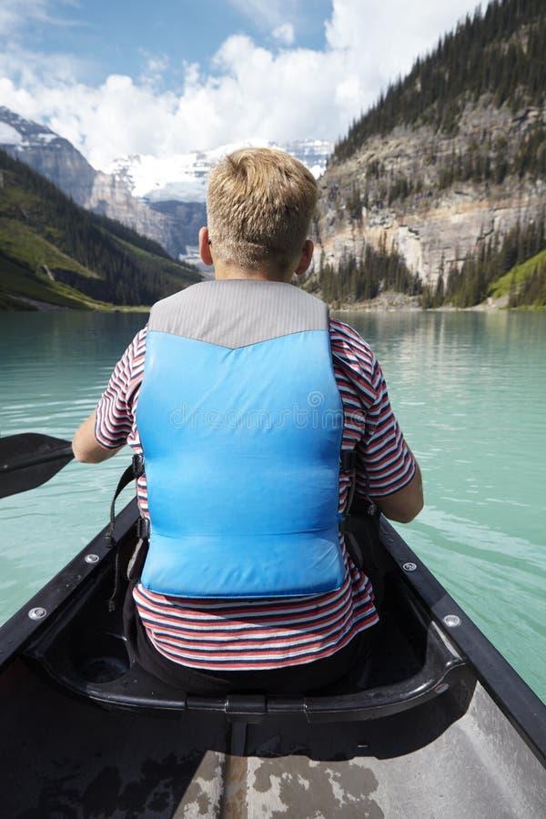 划皮船在美丽的湖的人背面图在阿拉斯加 库存图片