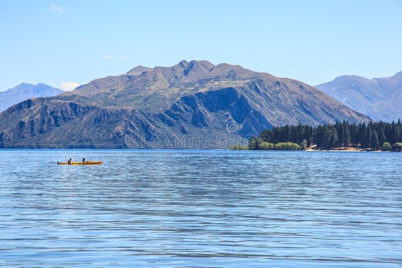 划皮船在美丽的自然湖的男人和妇女在夏天加热季节,围拢与山和森林背景 免版税库存照片