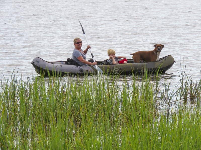 划皮船母亲、儿子和家庭的狗 免版税库存照片
