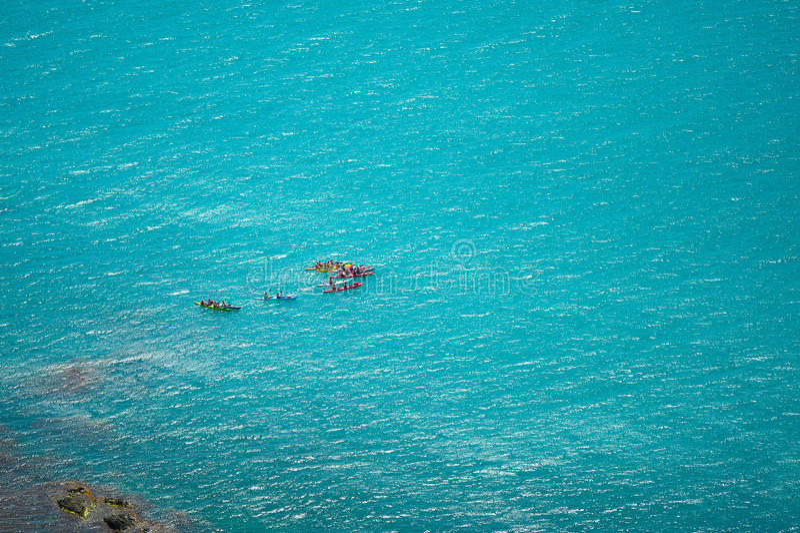 年轻划皮船的朋友获得乐趣在风景看法暑假 免版税库存图片