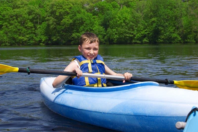 划皮船的男孩 图库摄影