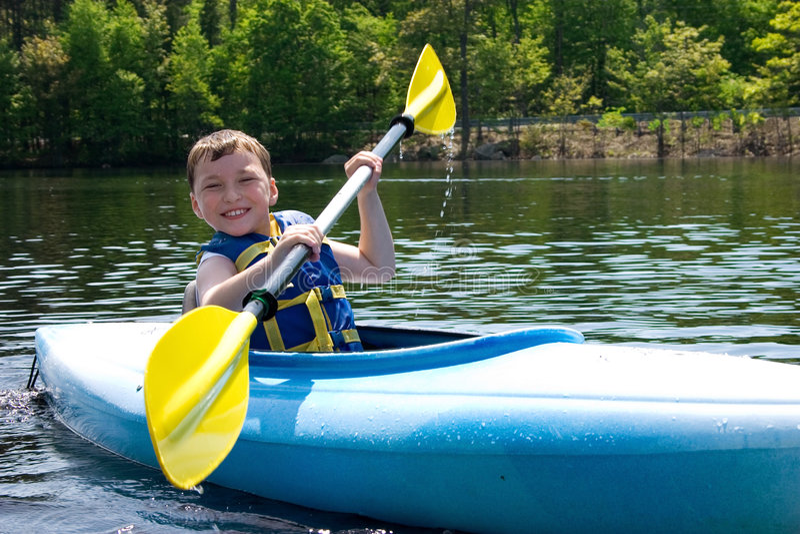 划皮船的男孩 免版税库存图片