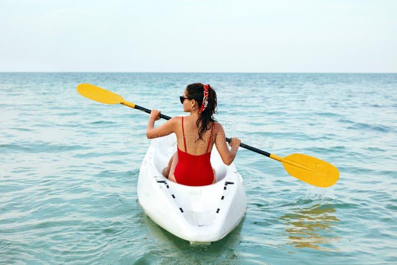 划皮船的 旅行在独木舟的妇女在海后面视图 免版税库存图片