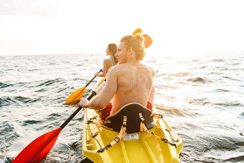 划皮船运动的有吸引力的夫妇 免版税库存图片