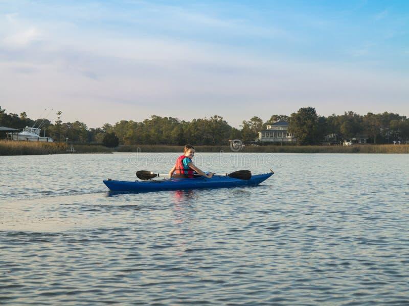 划皮船青少年的女孩的海 库存照片