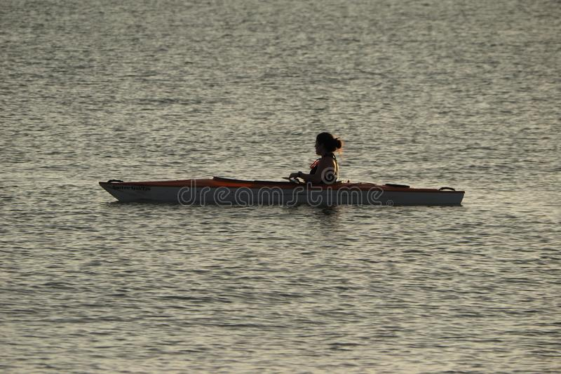 划皮船Captiva海岛的年轻女人在日落 库存图片
