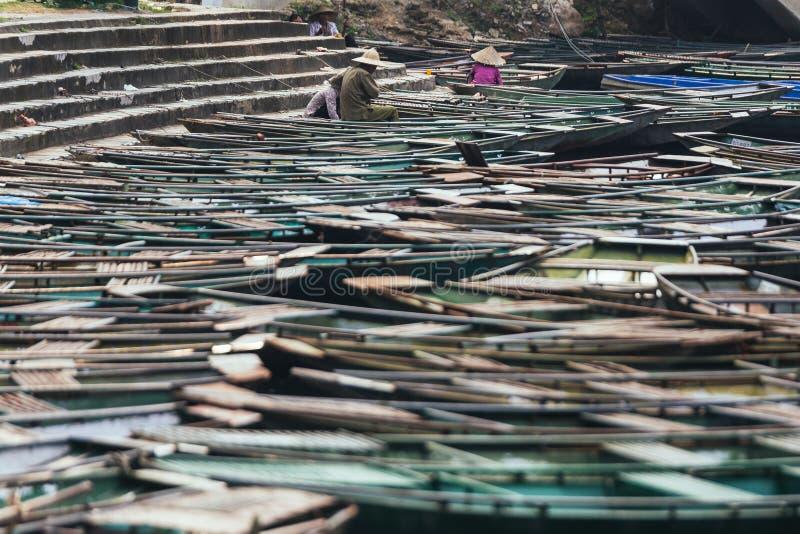 划船男人和妇女在小船在小船中止范围坐在河的有许多空的划艇的在夏天在的Trang洞穴 免版税库存图片