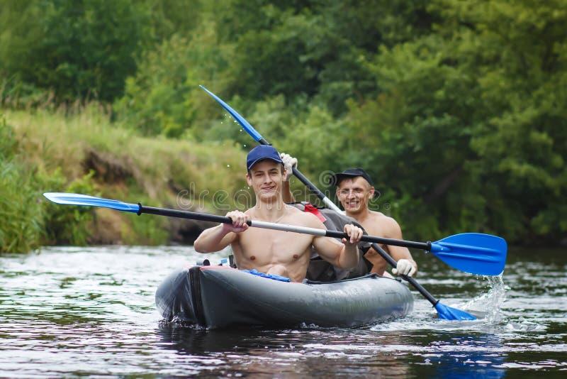 划船者沿皮船的河漂流 两个朋友在河的小船游泳并且荡桨在水的桨 免版税库存照片