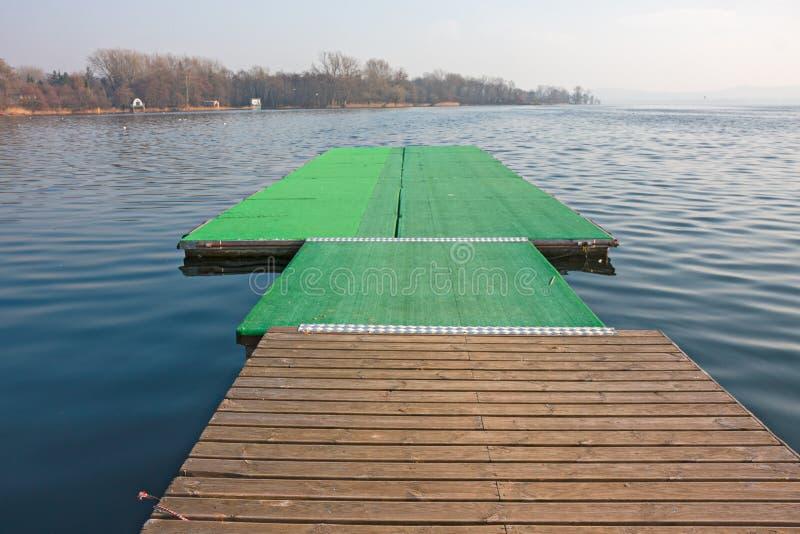 划艇相接船坞在岸的 免版税库存照片