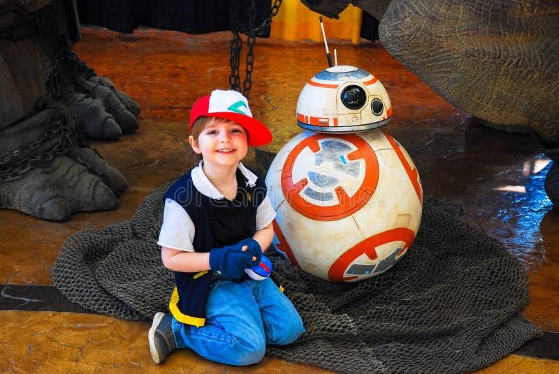 列克星敦, Ky美国- 2018年3月11日-在a.c.期间,可笑的列克星敦&玩具骗局年轻男孩摆在与从星际大战的机械机器人BB8 免版税库存图片