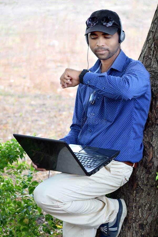 列出对与膝上型计算机的音乐的商人在公园 免版税图库摄影