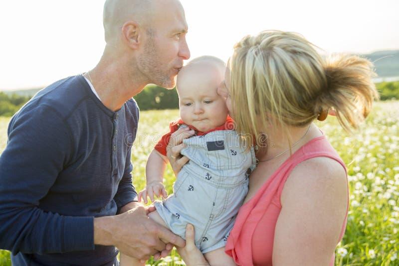 系列愉快三 使用外面在夏天的父亲、母亲和婴孩在日落时间 库存照片