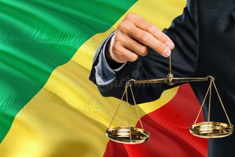 刚果法官拿着正义金黄标度有刚果共和国挥动的旗子背景 平等题材和法律 免版税库存图片