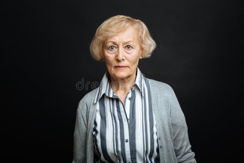 刚毅退休的妇女表示愤怒用黑色上色了演播室 免版税库存图片