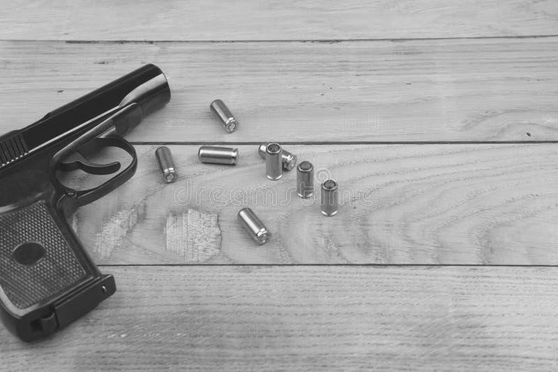 创伤木表面上的手枪用子弹和弹药筒,黑白 免版税库存图片