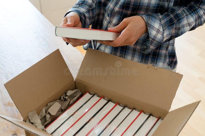 创作打开与她的新书样品的包裹并且检查精装书 免版税库存图片
