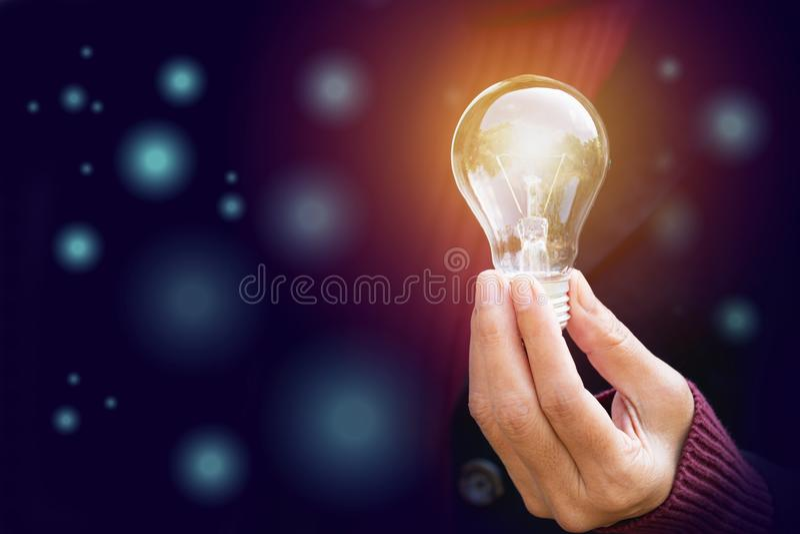 创新或手举行的创造性的概念在boke的一个电灯泡 库存照片