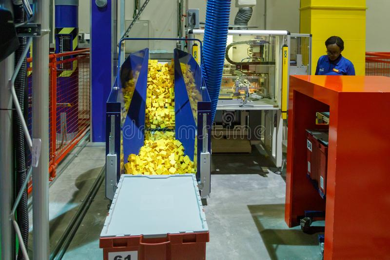 创造乐高砖的技术过程在Legoland 许多黄色砖乐高准备好对包装 免版税库存图片