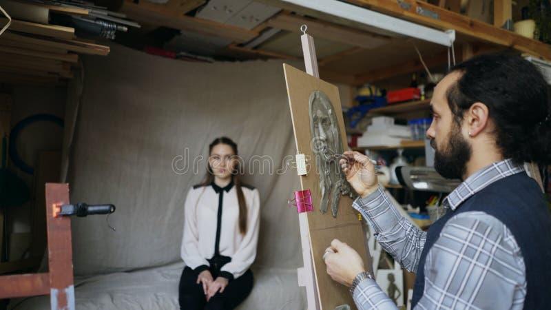 创造人的` s面孔的雕塑在帆布的雕刻家,当摆在他的少妇在艺术演播室时 免版税库存图片