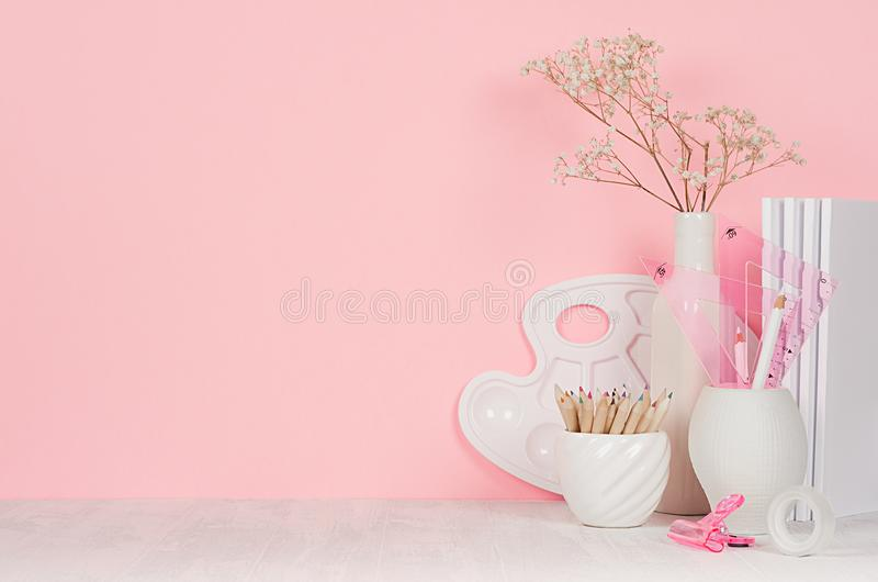 创造性女孩`的s -白色文具、调色板、铅笔在软的桃红色墙壁上和白色木书桌学校背景 免版税库存图片