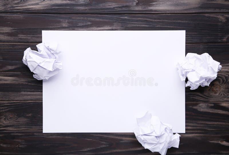 创造性概念、压皱纸和空白纸在棕色木背景 图库摄影
