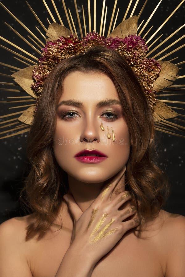 创造性的万圣节服装和组成在一名美丽的深色的妇女 在她的面孔的哀伤,疯狂的神色 顶头射击的艺术概念 免版税库存图片