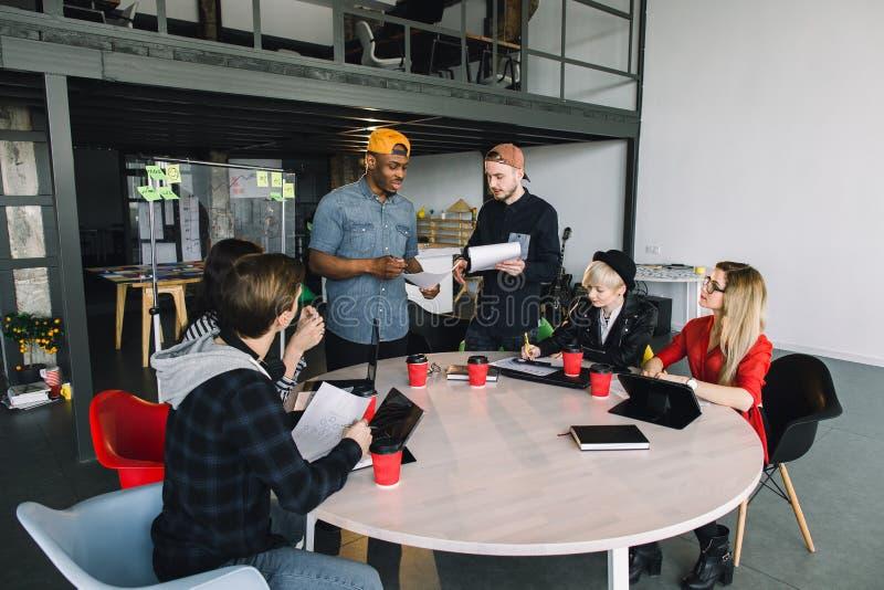 创造性的六位年轻multirational工作在办公室的商人和建筑师 免版税图库摄影