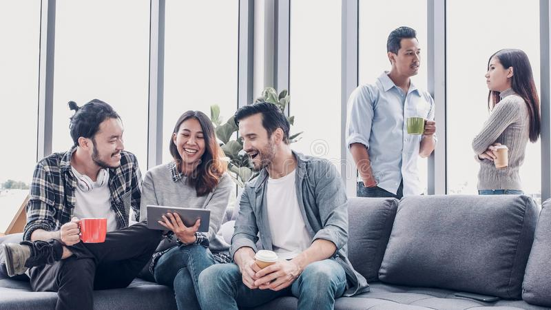 创造性的办公室,设计师开会在办公室放松和谈话在沙发 达从工作的一个咖啡休息 免版税库存图片