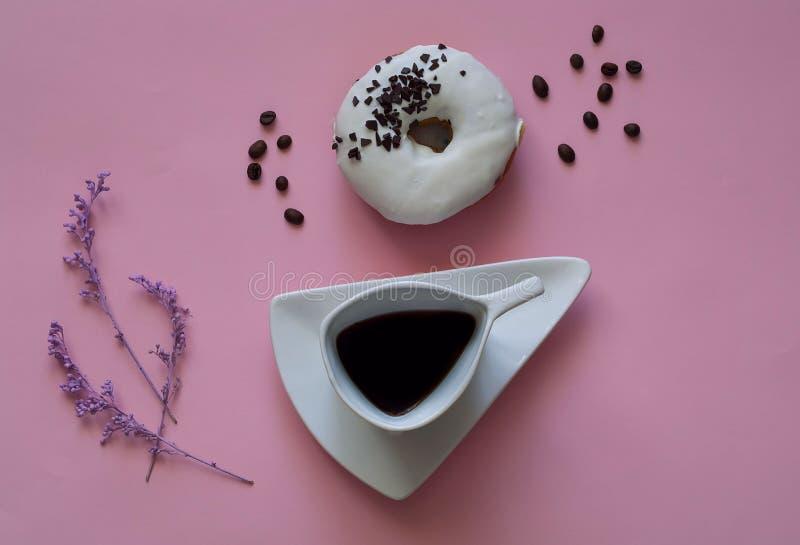创造性的咖啡和白色上釉圆环与黑巧克力甜点在桃红色背景 食物概念,五颜六色的早餐 免版税图库摄影