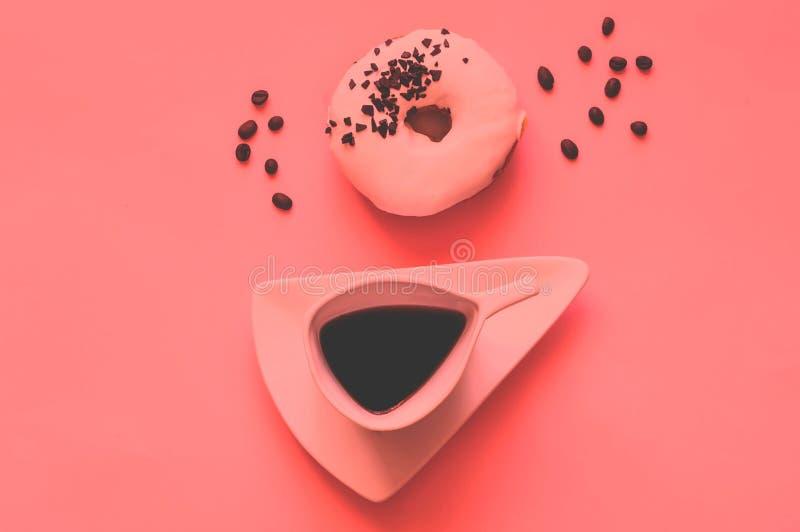 创造性的咖啡和白色上釉圆环与黑巧克力甜点在珊瑚背景 年2019年概念的颜色 图库摄影