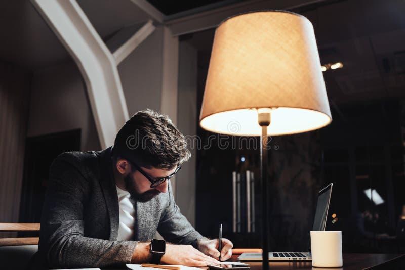 创造性的商人与纸张文件和当代膝上型计算机一起使用晚上在顶楼办公室 有胡子的年轻人坐b 免版税图库摄影