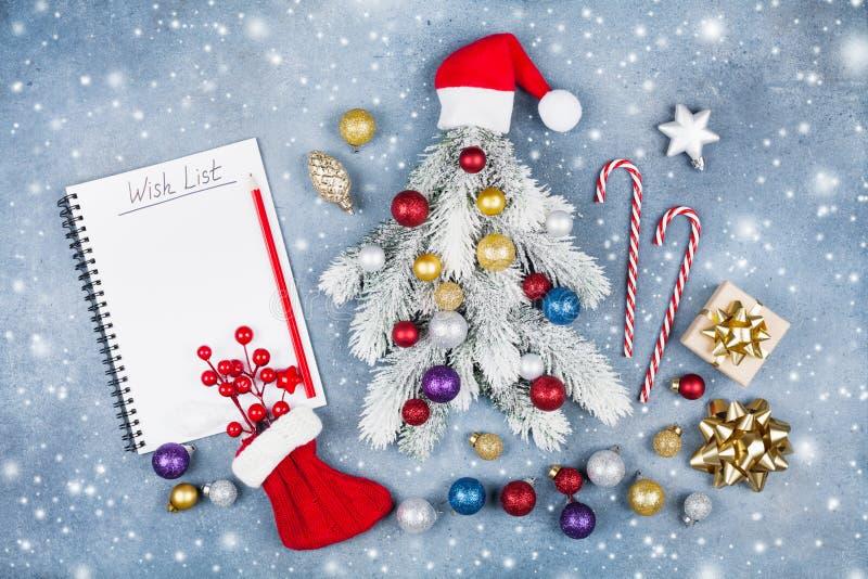 创造性的圣诞节杉树装饰了圣诞老人帽子、礼物盒和五颜六色的球与愿望在蓝色背景顶视图 平的位置 库存照片