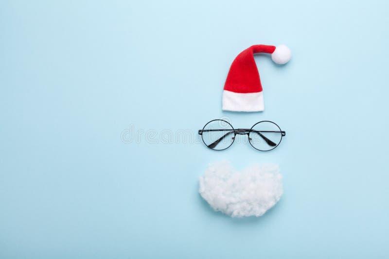 创造性的圣诞节构成 贺卡、邀请或者飞行物 圣诞老人帽子、胡子和玻璃在蓝色背景顶视图 免版税图库摄影