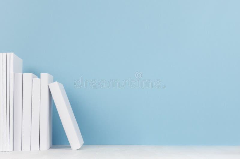 创造性的学校图书馆-荡桨在蓝色背景的白色空白的书 回到与拷贝空间的学校背景 库存图片