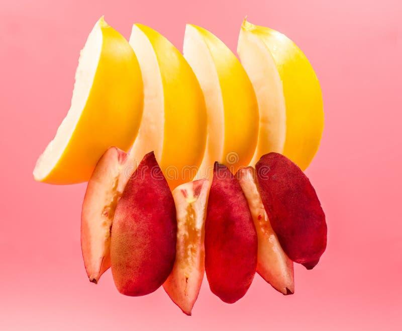 创造性的布局套瓜和桃子切垂悬在桃红色背景隔绝的天空中 免版税库存照片