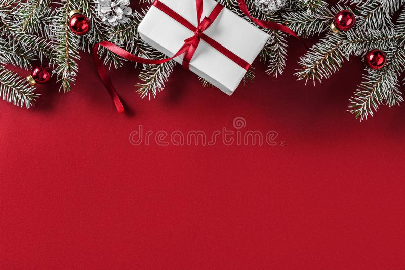创造性的布局框架由圣诞节冷杉分支,杉木锥体,礼物,在红色背景的红色装饰做成 免版税图库摄影