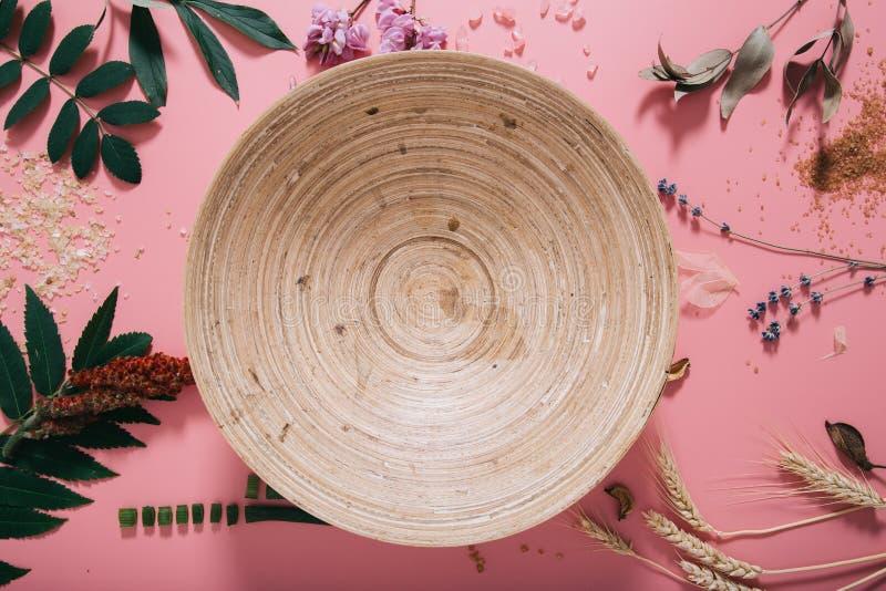 创造性的平的空的竹碗位置顶视图在淡色千福年的桃红色纸背景拷贝空间的 文本字法的模板 图库摄影