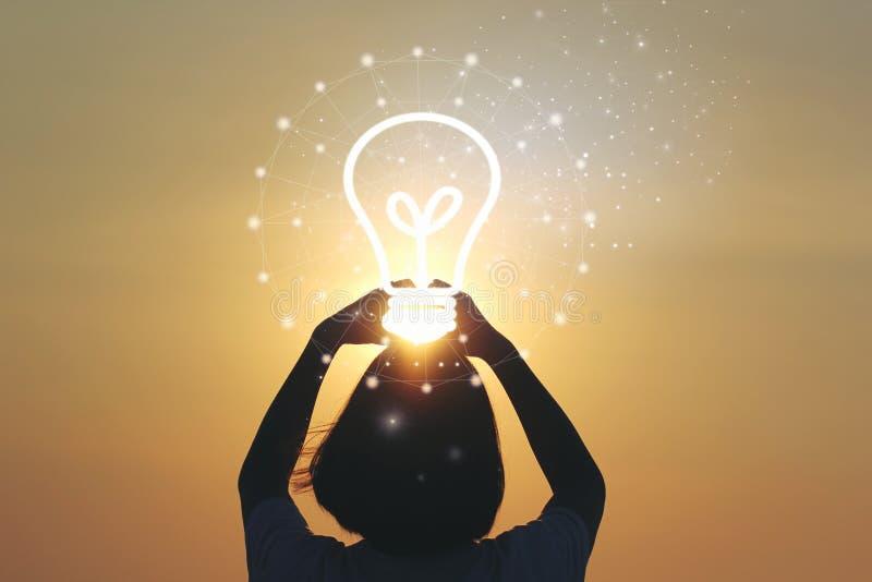 创造性的想法和创新概念,拿着在美好的日落背景的妇女手电灯泡 免版税图库摄影