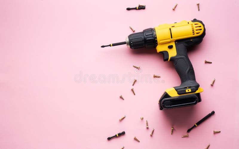 创造性的挑衅:在一个桃红色背景和小螺丝的一把黄色螺丝刀 图库摄影