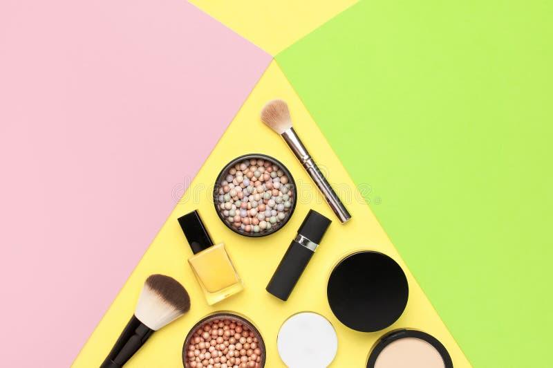 创造性的时尚背景 设置装饰化妆用品染睫毛油眼影膏脸红在五颜六色的构成刷子的粉末唇膏 免版税库存图片