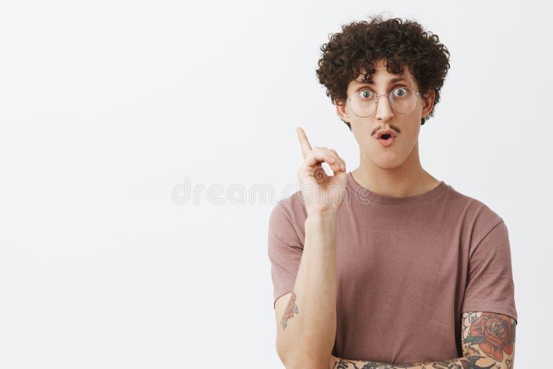 创造性的有髭卷曲举在尤里卡姿态的黑发和被刺字的胳膊的广告聪明的年轻人食指 库存照片