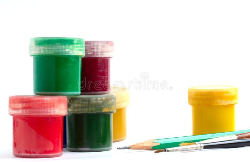 创造性的材料-瓶子五颜六色的树胶水彩画颜料刷子和铅笔 库存照片