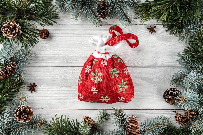 创造性的框架由圣诞树分支和杉木锥体做成在与圣诞节袋子的白色木背景 免版税库存图片