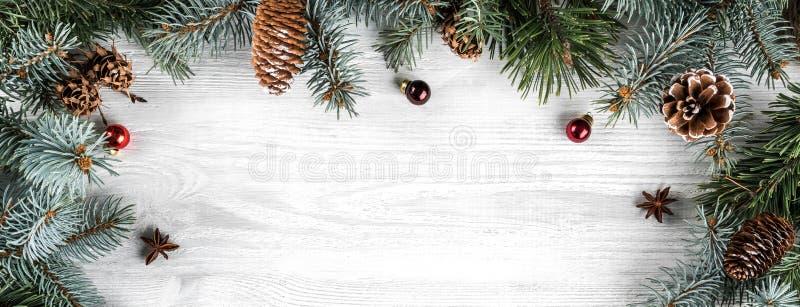 创造性的框架由圣诞节冷杉分支做成在与红色装饰的白色木背景 免版税库存图片