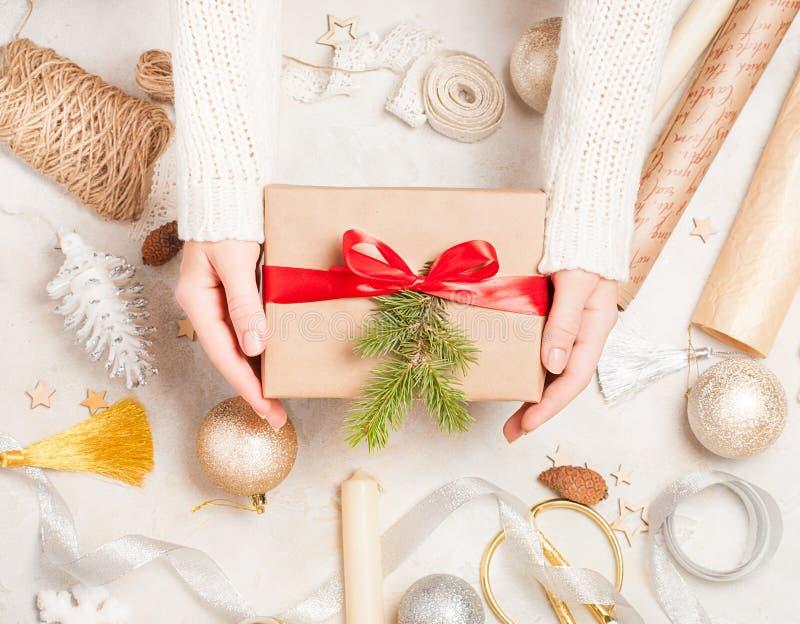 创造性的爱好 妇女` s手包裹在工艺纸的圣诞节假日手工制造礼物与麻线丝带 做在xmas礼物b的弓 免版税库存图片
