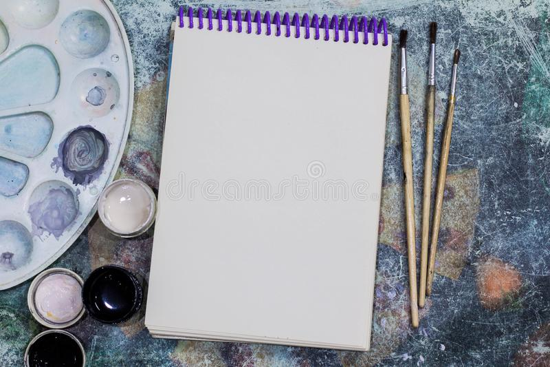 创造性的空间 艺术家的工作空间在破旧的桌上的:绘树胶水彩画颜料,笔记本,刷子 库存图片