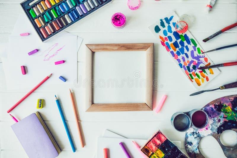 创造性的艺术家大模型顶视图明亮的工作场所  画的供应品种围拢的空白的帆布  艺术,车间, 免版税库存照片