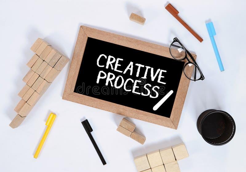 创造性的过程/创造性的过程顶视图在黑板有堆积作为步企业概念的台阶标志的木刻的, 免版税库存照片