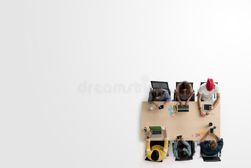 创造性的队小组的不同的人顶视图使用智能手机、片剂和计算机膝上型计算机的 天花板亚洲年轻创造性的s 库存照片