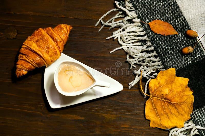 创造性的陶瓷咖啡舒适的用牛奶和新月形面包在木背景与格子花呢披肩,概念和温暖 复制空间 库存照片